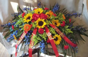Casket Spray with Delphinium, Sunflowers, Carnations, Large Gerbera Daisy and Solidaster