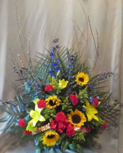 Traditional Tribute with Delphinium, Asiatic Lily, Sunflowers, Carnations, and Solidaster with Branch Accents