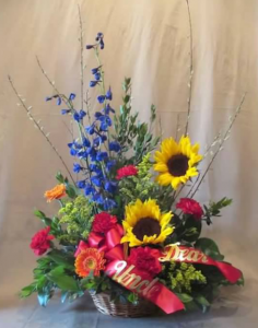 Fireside Basket with Delphinium, Large Gerbera Daisy, Sunflowers, Carnations, and Solidaster with Branch Accents