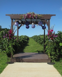 Gazebo with Purple Floral Swag and Ivy Draped Pedestals