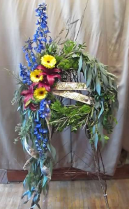 Wreath Tribute with Delphinium, Asiatic Lilies and Large Gerbera Daisy flowering on a wreath of mixed greens and field grasses with draping Eucalyptus