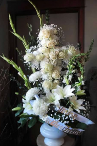 Cross Tribute with Snapdragons, Gladiolas, Football Mums, Asiatic Lilies, Large and Spray Roses, Hydrangeas, and Gypsophilia