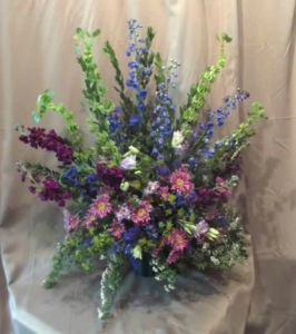 Traditional Tribute with Bells of Ireland,  Delphinium, Stock, Lisianthus and Daisy Mums