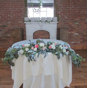 Head Table Arrangement with Pink and Ivory Roses, Eucalyptus, and Dusty Miller